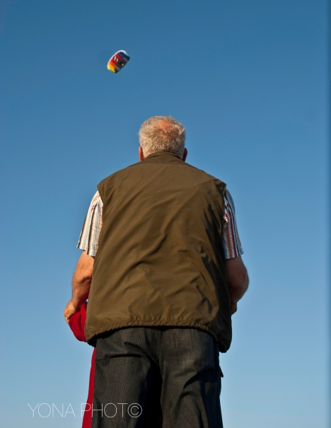 A granddad teaching his grandson how to fly a kite